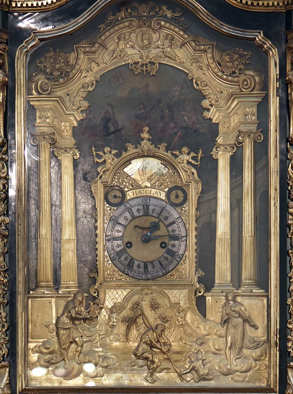 Close-up of the Clay clock. In the painted and cast bronze relief below we see Father Time, with hourglass and scythe, overcome by the power of music, which is represented by Apollo with his lyre and a woman personifying music